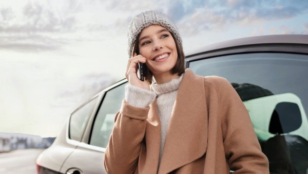 Lady on her phone outside her car in the winter smiling