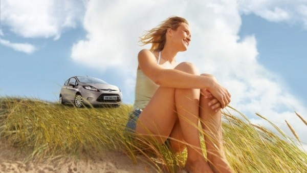 Lady on a beach with her Ford Fiesta