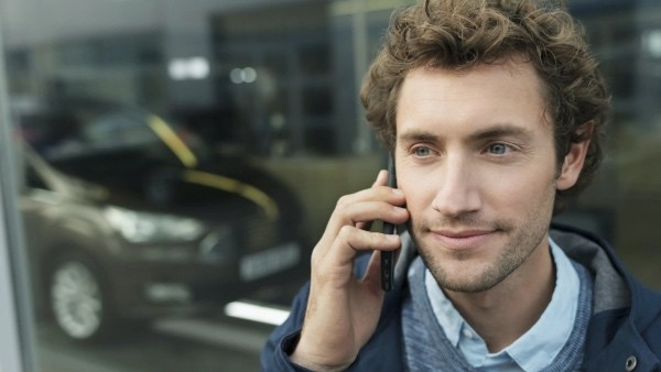 A man on phone outside Ford showroom